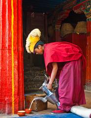 A monk pours butter tea in Tashilhunpo Monastery, Tibet.